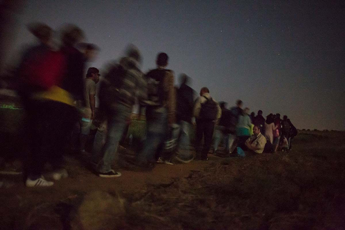 Evzoni, July 5, 2015. Ahmad and Jihan join a group of about 200 migrants to go across the border with Macedonia. Greek militants have just given them a direction to avoid police and bandits.
