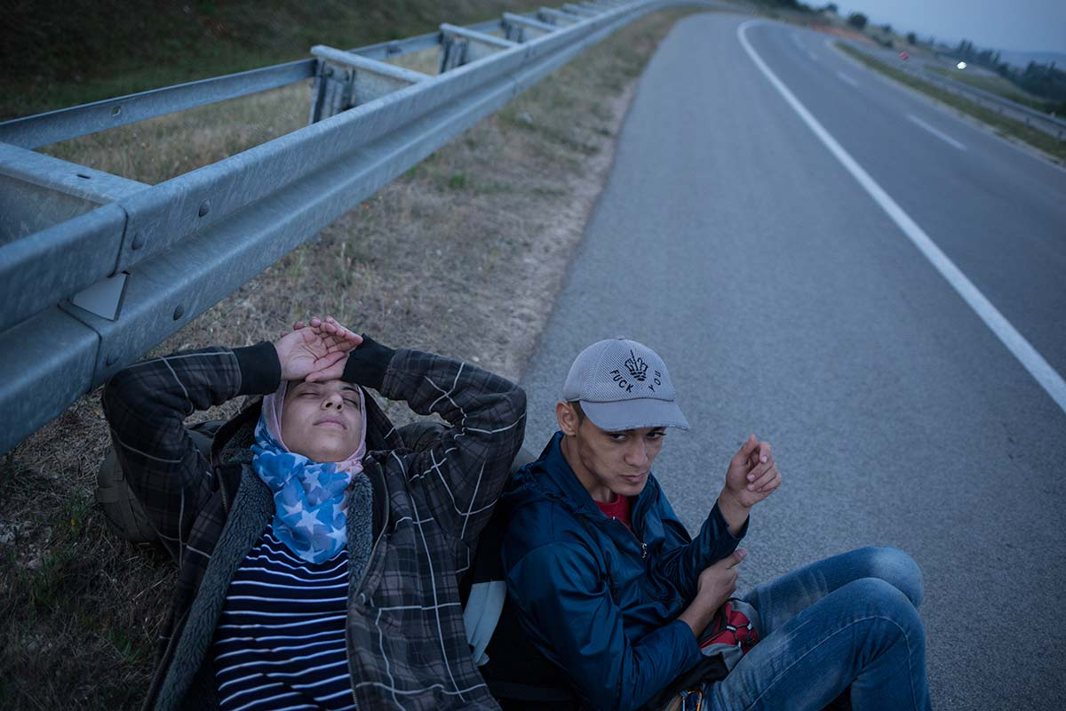 Serbia, highway E75, July 8, 2015. Jihan, exhausted by the night walking between Macedonia and Serbia, is sleeping on the emergency line of the highway going across the border.