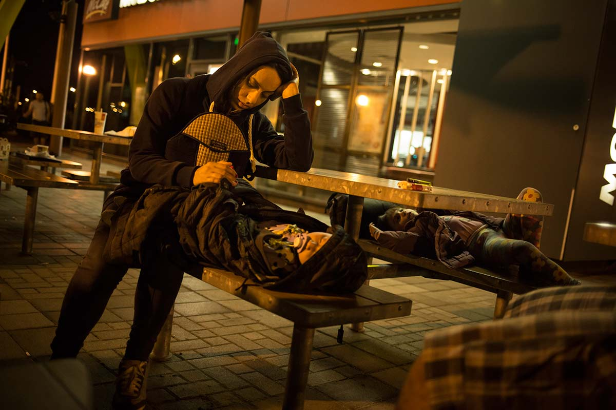 Budapest, July 16, 2015. Jihan sleeps outside of a Macdonalds in the suburbs of Budapest, the hungarian capitale. Two drivers, paid by a smuggler, have just dropped her group here after driving them away from the border.