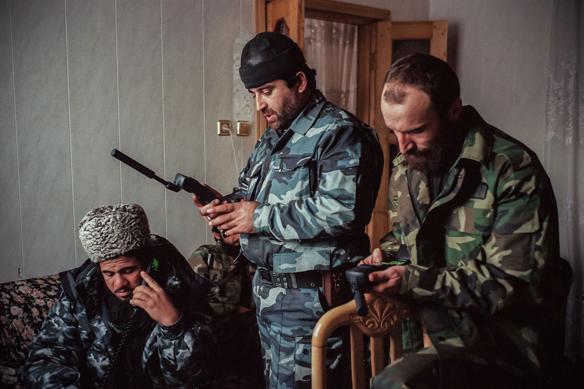 December 13th 1999.  Amir Khattab (on a mobile telephone), wearing the typical astrakhan hat of the region; Commandant Sayed and Shirvani Baseyev, brother of Shamil, checking their mobile phones.